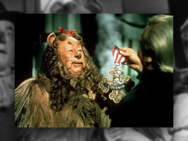 A still scene of the lion getting a medal from the Wizard of Oz.