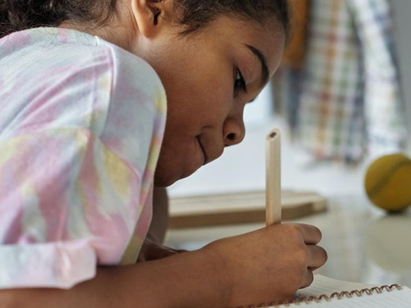 Young girl writing on paper